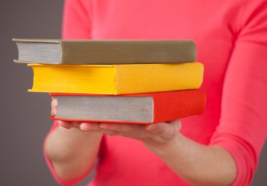 Unrecognizable young woman holding three books