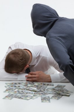 Robber bending over the businessman and money