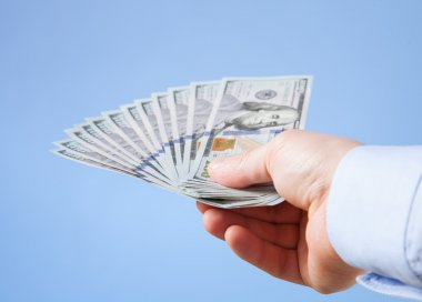 Businessman's hand reaching out dollars