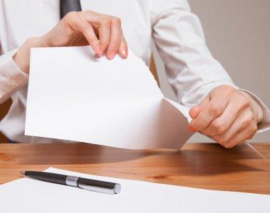 Unrecognizable businesswoman tears sheet of paper