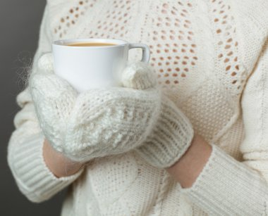 girl hands in mittens with cup