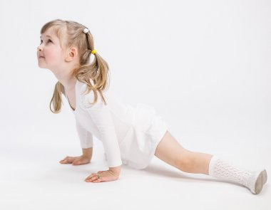 Smiling little girl doing the splits