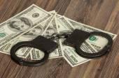 Handcuffs and money bills