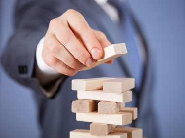 businessman forming a wooden pyramid