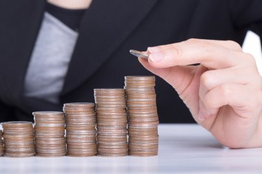 Business women put coin stack money