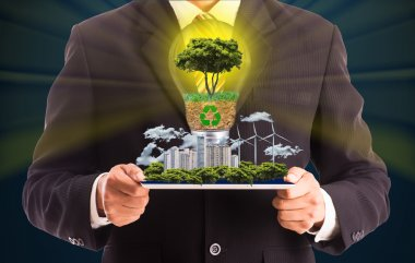 Businessman hold tablet for show green city