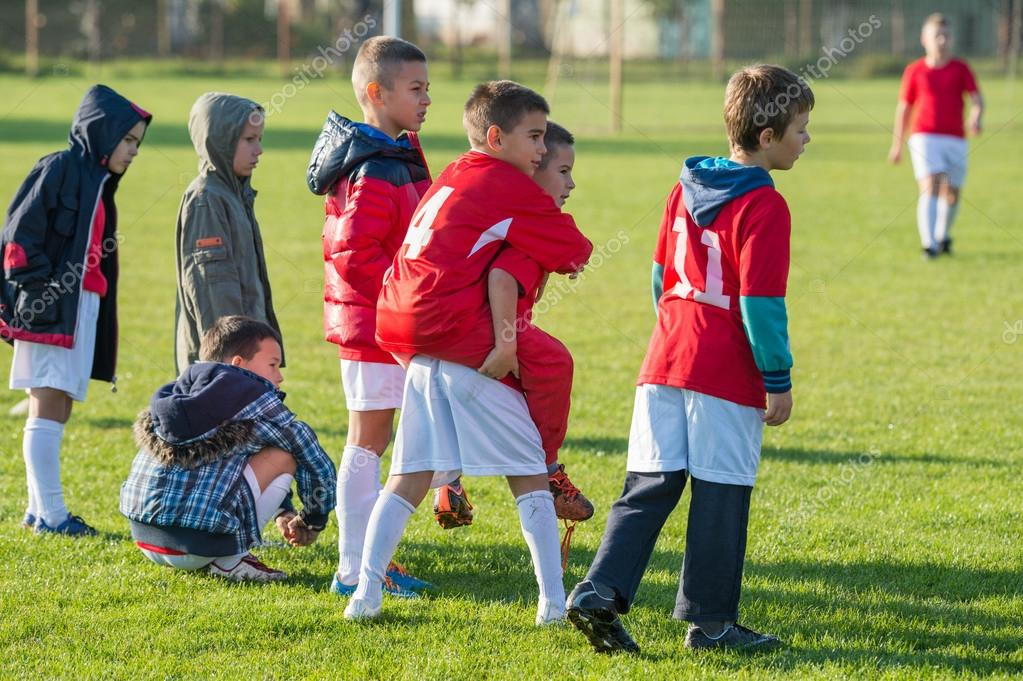 Young boy watching a kids soccer match.