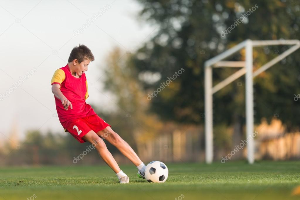 kid kicking a soccer ball