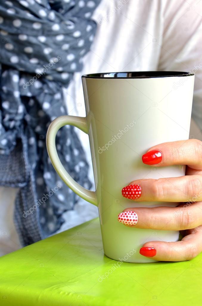 Chica con uñas rojas en los dedos sostener taza blanca, closeup ...