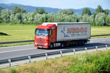 Red moving Mercedes-Benz Actros truck coupled with semi-trailer located on slovak D1 highway surrounded by green field and trees.