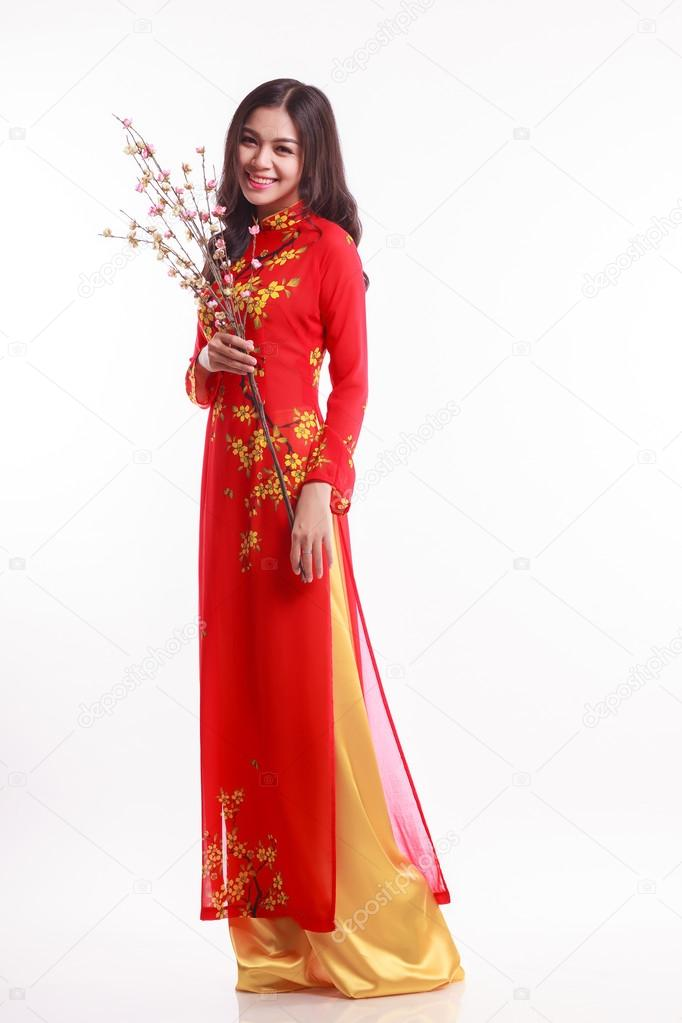 Beautiful Vietnamese woman with red ao dai holding cherry blossom for celebrate lunar new year