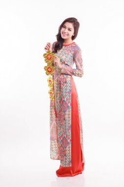 Beautiful Vietnamese woman wearing impression ao dai holding lucky decorate object for celebrate lunar new year