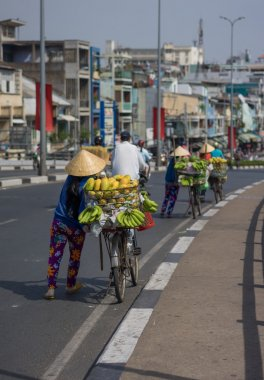 Typical street fruit vendor with palm-leaf conical hat moving at the street in road.