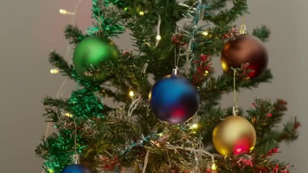 Žena zdobí vánoční stromek s ochrannými obličejovými maskami jako symbol pandemie v novém roce.