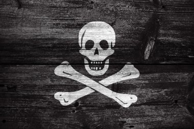 The traditional Jolly Roger of piracy Flag, painted on old wood plank background