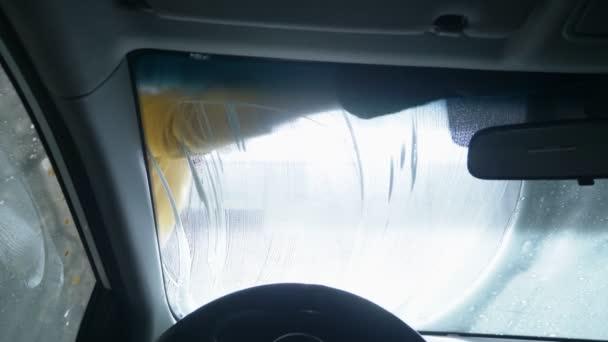 pohled zevnitř auta. muž myjící auto v myčce aut
