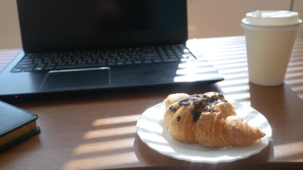A desk with a disposable cup for coffee and fast food. open laptop computer. breakfast in the office