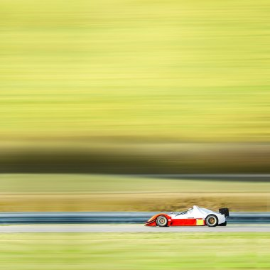 Formula one race car on speed track - motion blur background wit