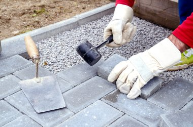 Bricklayer places concrete paving stone blocks for building up a