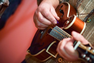 close up hands senior man playing mandolin