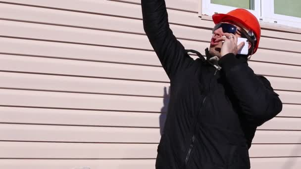 Dělník na stavbě v zimě na smartphone, mával rukama, řízení provozu