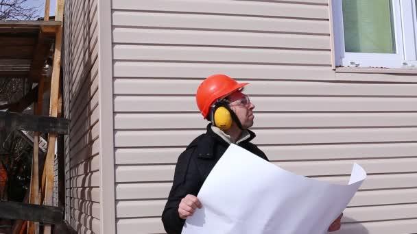 Dělník na stavbě, v zimě se dívá na výkres a porovnává práce