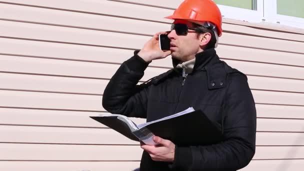 Dělník na stavbě v zimě na smartphone