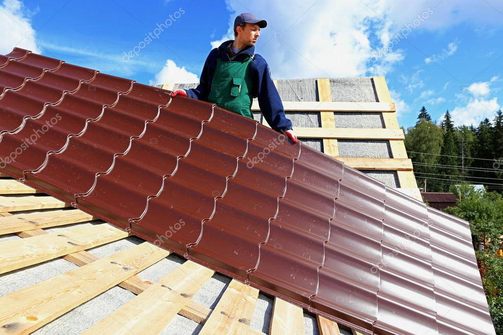 Worker puts the metal tiles on the roof