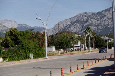 Kemer, Turkey - May 24, 2021: Turkish street view: mountains, green nature, homes and cars on sunny day. Lifestyle view. High quality photo