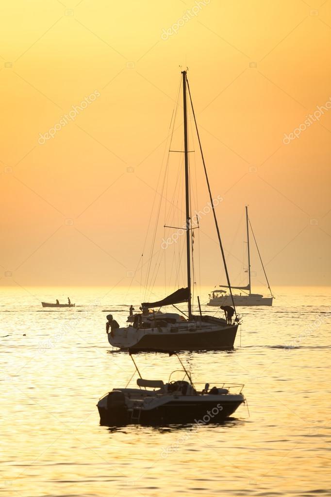 Boats sailing at sunset
