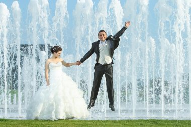 Newlyweds in front of water fountain