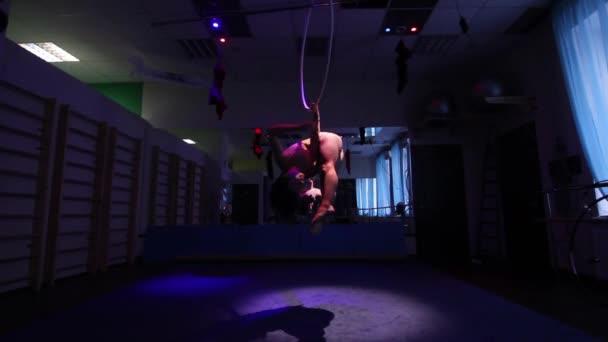 Légi Akrobata nő cirkusz porondon. trükk abroncs kék háttérrel