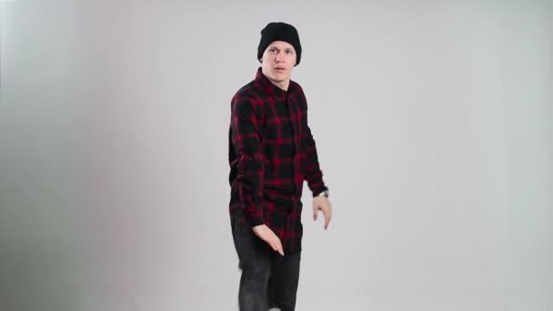 Ballerino hip-hop in danze tappo nello studio della foto con sfondo grigio