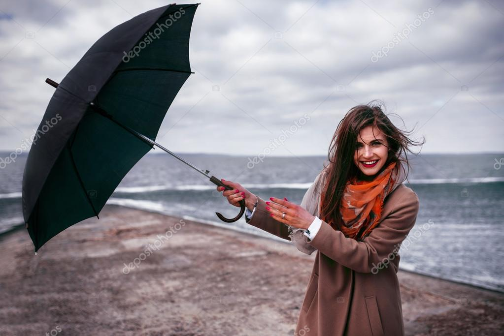 Redhead girl with umbrella by the sea