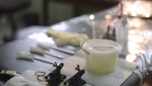 Tetovací umělec připravují inkoust kontejnerů před zahájením práce tetování