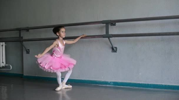 little ballerina puts on pointes  in the ballet hall