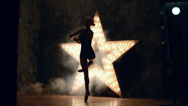 elegantní baleríny dělat cvičení v učebně. Kouř, mlha, dívka v pointe, víry kolem vás