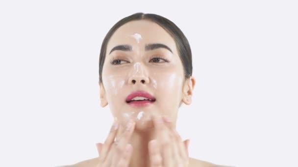 Szépség koncepció. Egy fiatal ázsiai nő krémet tett az arcára. 4k felbontás.