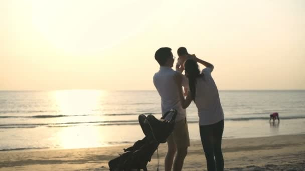 Family concept. Parents playing with babies on the beach. 4k Resolution.