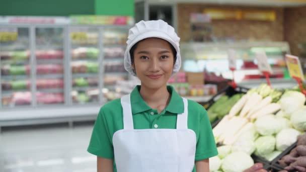 Shopping-Konzepte mit 4k-Auflösung. Eine Asiatin verkauft in einem Kaufhaus selbstbewusst Gemüse.