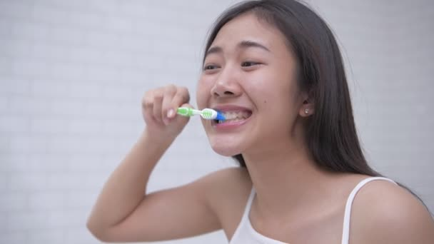 Daily routine concept of 4k Resolution. Asian woman brushing teeth in the bathroom.