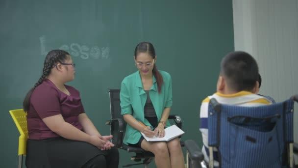 Oktatás koncepciója 4k felbontás. A tanár fogyatékos gyerekekkel találkozik az osztályteremben..