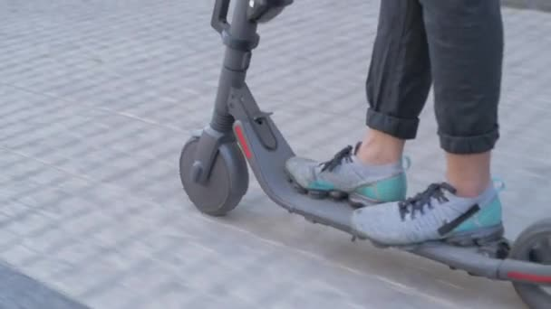 Energy efficient travel vehicle concept of 4k Resolution. close up riding a scooter on the sidewalk.