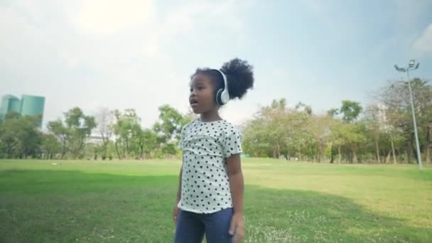 Holiday concept of 4k Resolution. Young girls listening to music happily in the garden.