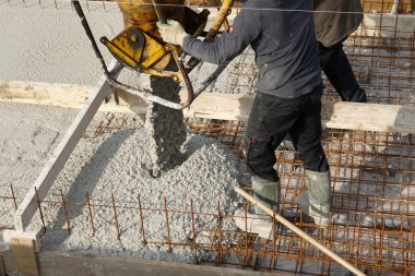 Constructon workers with yellow helmet on a concrete floor