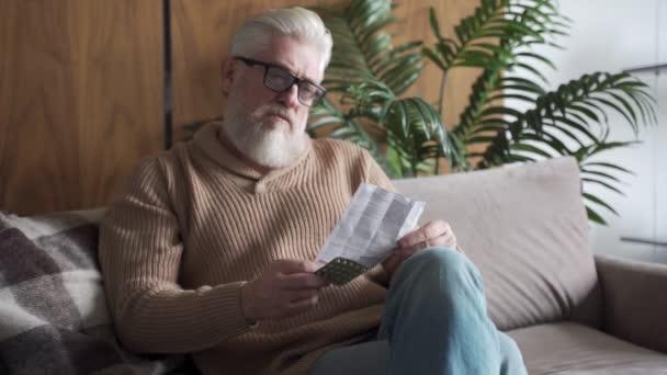 Älterer Mann sitzt krank mit Brille auf Sofa und liest Anleitung zur konzentrierten Einnahme von Tabletten