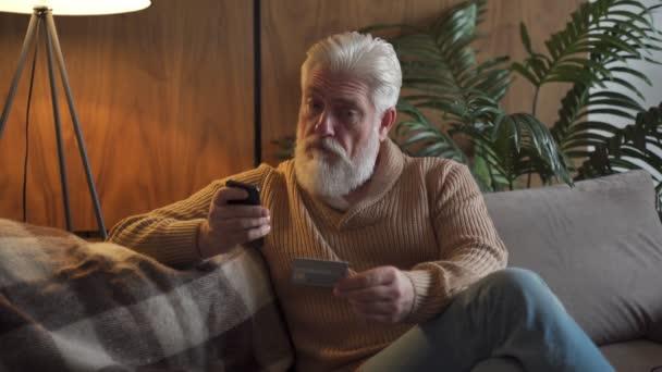 Důchodce platí on-line pomocí kreditní karty a aplikace z chytrého telefonu. Starší osoba používající internetovou platbu domácí banka nakupování s moderní technologií
