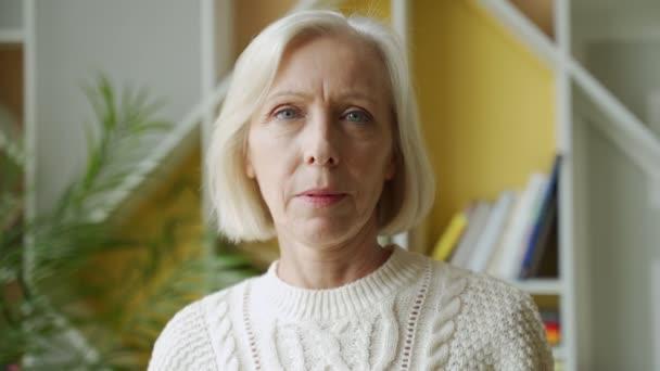 Mosolygó középkorú érett ősz hajú nő néz kamera, boldog idős hölgy pózol otthon beltéri