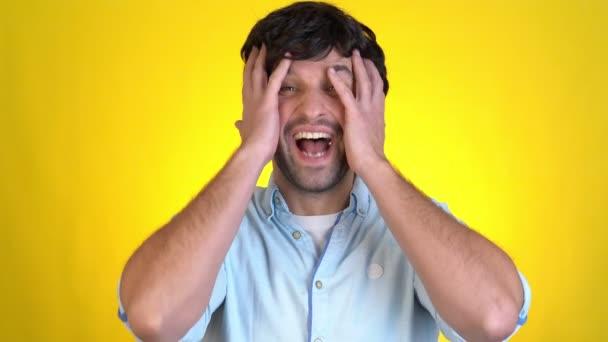 Junger Mann posiert isoliert auf gelbem Hintergrund im Studio. Menschen Emotionen Lifestyle-Konzept. Blicke Kamera schockiert sagen, wow Hände aufs Gesicht gelegt