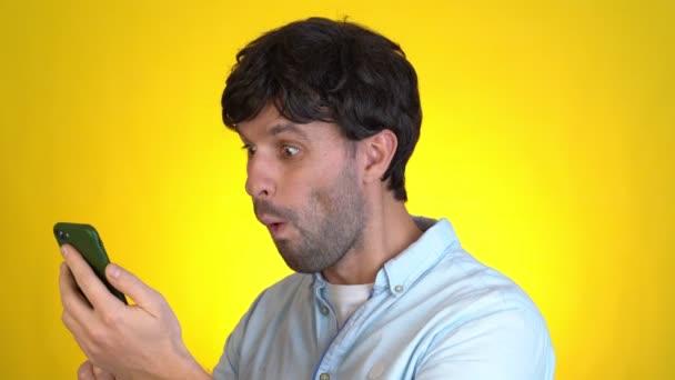 Lustige junge Mann posiert isoliert auf gelbem Hintergrund Studio. Menschen Lifestyle-Konzept. Mit Handy-Eingabe von SMS-Nachricht Surfen sagen wow bedecken Mund mit geöffnetem